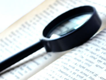 a book being magnified with a looking eye glass